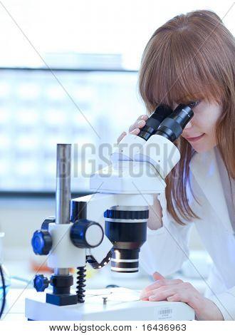 pretty female researcher using a microscope in a lab