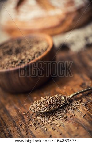 Cumin.Caraway seeds on wooden table. Cumin in vintage wooden bowl and vintage spoon.