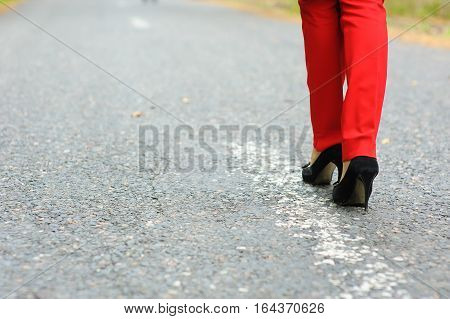 Lonely girl on the road. Lonely girl walking along the road. Road markings.