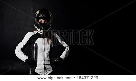 Femail moto rider portrait on black background. Sport and extreme girl in motocycle equipment. Copy space for advertising text or biker goods.