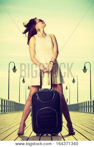 Travel packing journey concept. Woman wearing white short dress standing next to her suitcase with windblown hair pier in background.