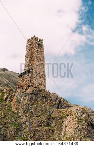 Ancient Old Stone Watchtower On Sky Background In Pansheti Village, Kazbegi District, Mtskheta-mtianeti Region, Georgia. Spring Or Summer Season. Famous Landmarks And Places In Kazbegi District.