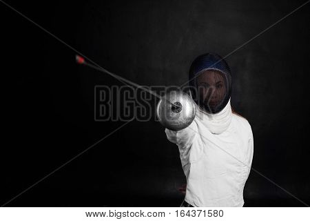 Fencing sport concept. Girl in white costume with sword in one hand on black background. Copy space for advertising goods or text.