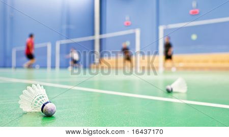 badminton - badminton courts with players competing; shuttlecocks in the foreground - shallow DOF