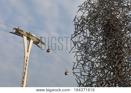 Gondola lift with clear sky above. Silhouette of air-cable cars next to huge metallic structure.