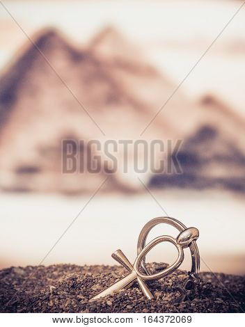 The Egyptian ankh is a cross in the sand against the backdrop of the Great Pyramids. Photo toned.