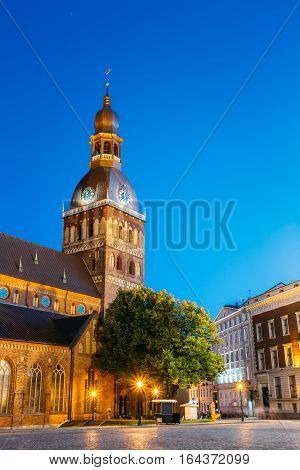 Riga, Latvia. View Of Dome Square And Dome Cathedral In Evening Illumination Under Blue Sky. Ancient Medieval Monument Of Old Town, Architectural Heritage, Famous Showplace.