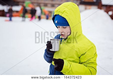 Child drinking hot tea from the metal mug. Wintertime