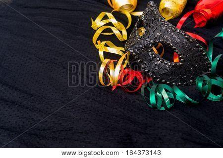Mask with masquerade decorations on dark silk background