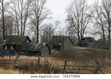 Sad cloudy landscape with abandoned houses in the village Paltsevo. Russia, Tver region, Bologovsky District.
