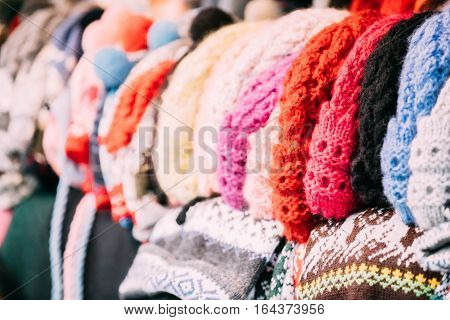 Close View Of Various Colorful Traditional European Warm Clothes - Caps, Hats At Winter Christmas Market. Souvenir From Europe.