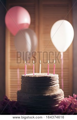homemade delicious sweet dessert with baloons; birthday cake with firing candle on wooden background;
