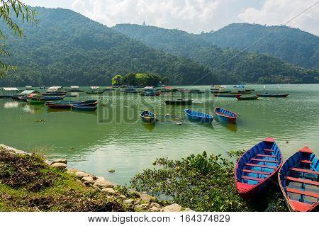 Colorful boats at shore. Lake Phewa in Pokhara, Nepal.