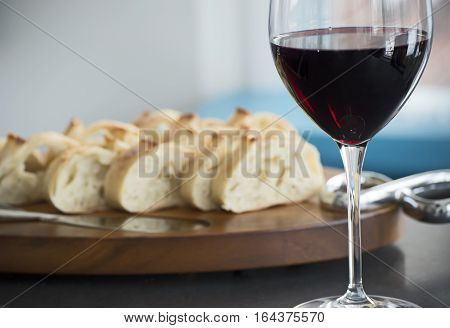 Glass of red wine with wood serving platter with french baguette healthy lifestyle, relaxing tranquil scene, romance or wine tasting and food pairing social image with room for copy