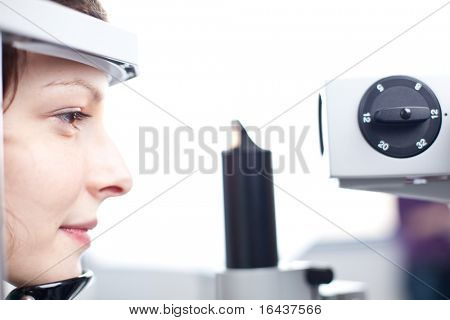 optometry concept - pretty young woman having her eyes examined by an eye doctor (color toned image)