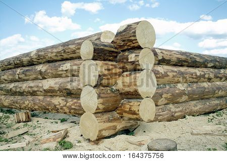 Beginning of rural house construction from heavy logs against blue sky with white clouds in summer day
