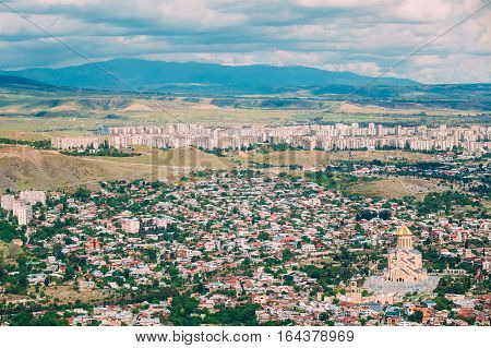 Tbilisi, Georgia. The Aerial Panoramic View Of Sameba Complex, Holy Trinity Cathedral Surrounded By Populous Private Residential Area. Hilly Cityscape In Summer Sunny Day Under Blue Cloudy Sky.