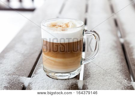 Cup with cappuccino coffee on the wooden bench covered with snow.