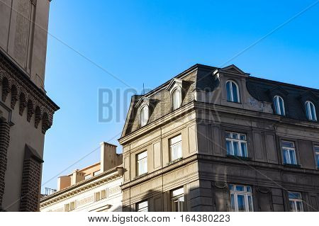 Old residential tenement houses during sunset. Bright warm afternoon light. Blue sky.