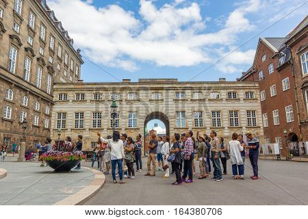 Copenhagen, Denmark, July 20, 2016, Asian tourists standing in front of  the Danish Parliament. They take part in a  guided tour.