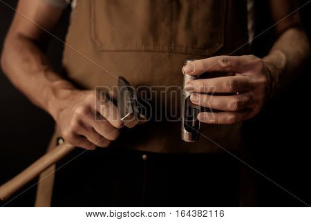 Hands holding leather craft object with tool using for leather manufacture