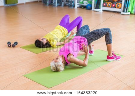 Women training their glutes by doing bridging exercise on mats in gymnasium.