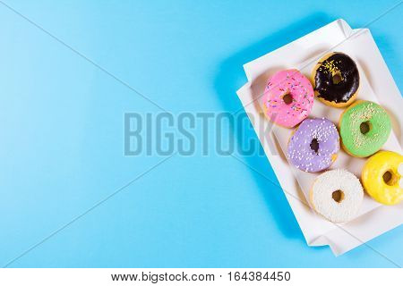 Six colorful round donuts in the box with copy space. Flat lay, top view. Pastel shades