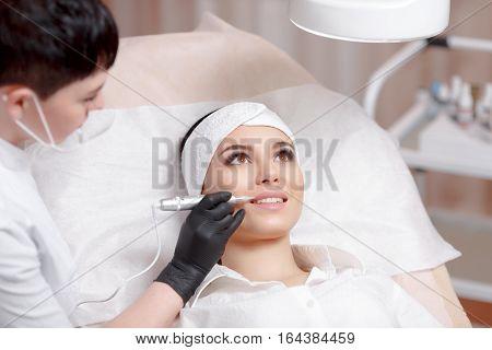 Permanent makeup lips. Permanent makeup wizard makes lips correction procedure. Beautiful young woman gets lips correction procedure. Makeup in a beauty salon