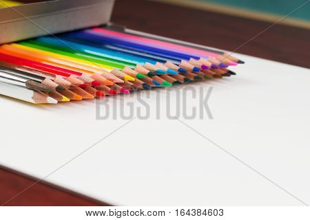 Multicolored pensils in the box on a wooden table. Back to school. Copy space.