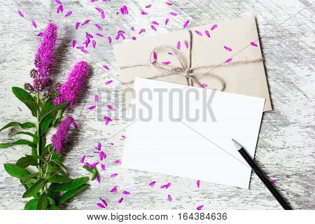 Blank white greeting card and envelope with lilac wildflowers and pencil mock up on white rustic wood background for creative work design. top view