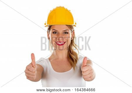 Picture of a sexy young woman wearing a protection helmet showing thumbs up - isolated background