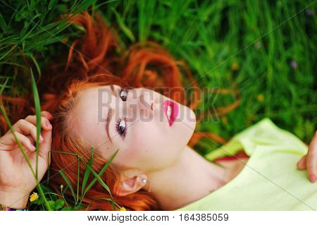 beautiful red-haired girl in a yellow shirt lying on the grass and stares dreamily