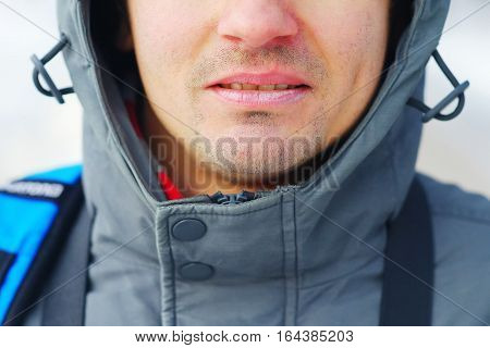 Closeup of a well-groomed man's face. Care for chapped lips in the cold season. Concept of a healthy lifestyle.