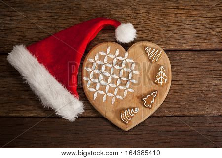 Various ginger bread on wooden board decorated with santa hat during christmas time