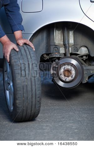 mechanic changing a wheel of a modern car (shallow DOF; color toned image)