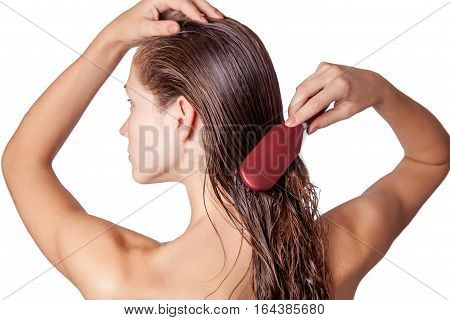Young beautiful woman with white towel and freckles combing her brown wet hair after showering. studio shot. isolated on white background.