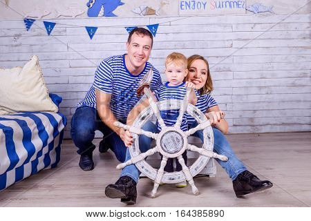 Happy Family In Sailor T-shirts Playing With Steering Wheel Indoors. Travel And Adventure Concept. S