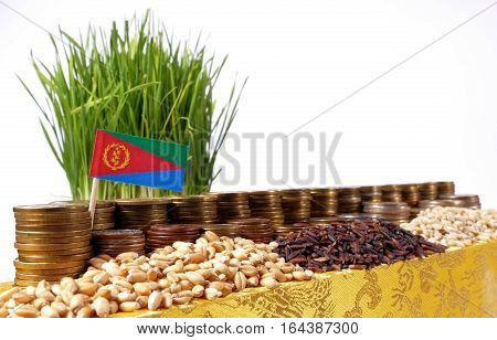 Eritrea Flag Waving With Stack Of Money Coins And Piles Of Wheat And Rice Seeds