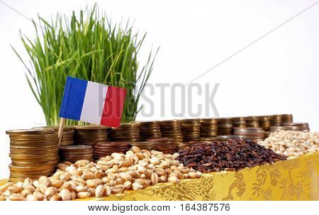 France Flag Waving With Stack Of Money Coins And Piles Of Wheat And Rice Seeds