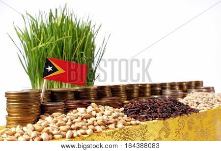 East Timor Flag Waving With Stack Of Money Coins And Piles Of Wheat And Rice Seeds