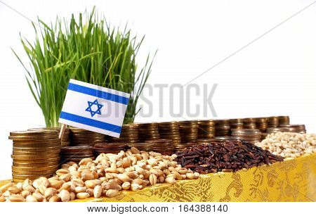 Israel Flag Waving With Stack Of Money Coins And Piles Of Wheat And Rice Seeds