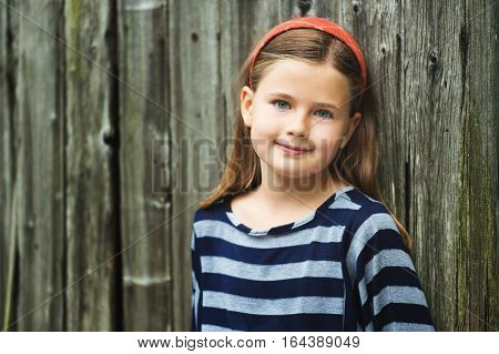 Outdoor portrait of cute little 8-9 year old girl with brown hair, wearing stripe top, standing against old wooden background