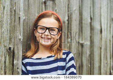 Outdoor portrait of a cute little 9 year old girl wearing eyeglasses