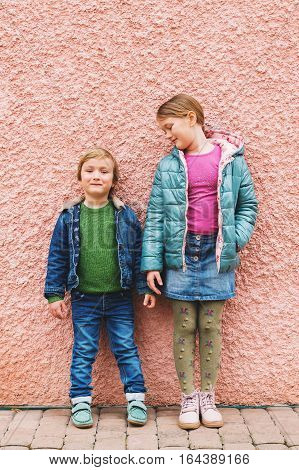 Fashion portrait of adorable kids wearing warm jackets and shoes