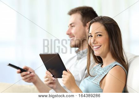 Couple watching tv sitting on a sofa in the living room at home. Man is zapping and the woman is holding a tablet and looking at you