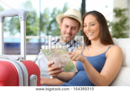 Couple of tourists searching location in a map during vacations sitting on a couch of an hotel or apartment