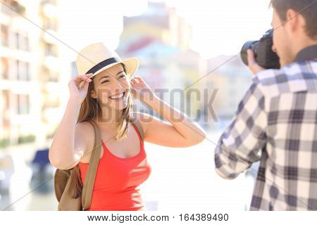Tourist photographing his girlfriend wearing red shirt in a travel destination on vacations