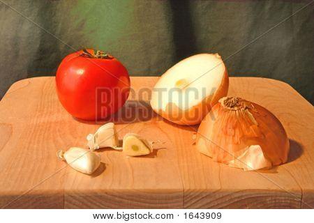 Tomato, Onion, And Garlic On A Cutting Board