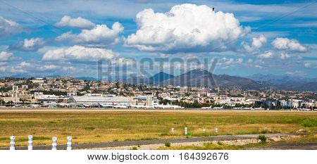 Nice, France - September 15, 2016: panoramic view of Nice airport against of mountains and cloudy sky. The cote d'azur landscape