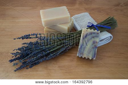 Four bars of goats milk soap on a light wooden table with a bouquet of dried lavender and a folded ramie washcloth. Natural light and shallow depth of field. The lavender soap with purple swirls is in the foreground.